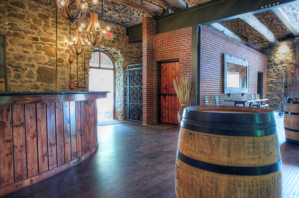 Wine barrels mixed with old stone, wooden beams, incandescent light, and swathing sunlight create the perfect mood.