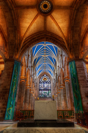 A symmetrical wide angle photo of St. Giles Cathedral pillars, stained glass, altars, and old stone.