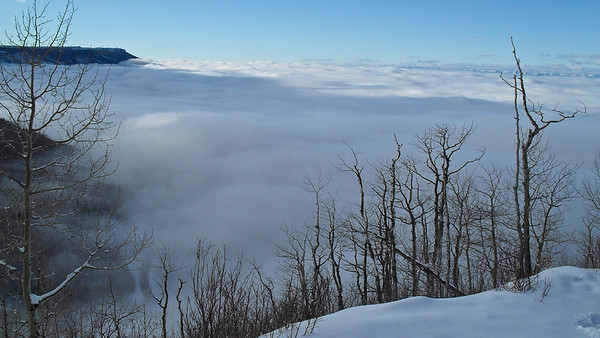 the Road Down Below... Grand Mesa, Colorado. Clouds and fog filling into the valleys of Grand Mesa. You can see Hwy 65 in the lower left 1/3 of pic. Shot from higher on Hwy 65.