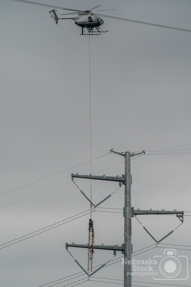 5-20-2018<br /> 140/365<br /> A crew checks out the high voltage transmission lines north of Norfolk Sunday afternoon. Yes.....there is a guy on top of the ladder that is tied off riding the ladder down to the ground from the helicopter.<br /> Photo taken with a Sony A9 with a Sony FE 100-400<br /> ISO 250<br /> 1/400th at F11<br /> (96471)