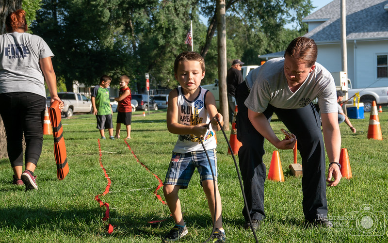 """8-7-2018<br /> 219/365<br /> """"National Night Out""""<br /> Its always fun helping out with this event. Here in the picture shows members of the Norfolk Fire Reserves running young kids through a """"Combat Course"""". Kids love the interaction with the Firefighter and Police officers of the community. <br /> Photo taken with a Sony A6300 with a Sony 18-200<br /> ISO 125<br /> 1/500th at F4.5<br /> (137800)"""