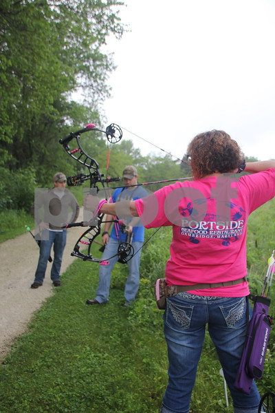 The 3-D Archery Shoot took place at Kennedy Park on Saturday, June 13, 2015 and will end on Sunday, June 14, 2015. Left to right: Jacob Asche and Dave Schott look on as Tracy Reed takes her shot at one of many  3-D targets set up at the archery event.