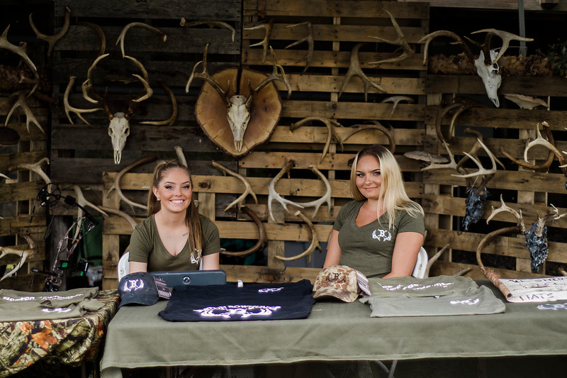 Allie Fini and Taylor Eyles sell merchandise during the 3D bow hunting event that was held at Hollis Hills Farm, co-sponsored by Boston Bow Hunters, on Saturday, July 22, 2017. SENTINEL & ENTERPRISE / Ashley Green