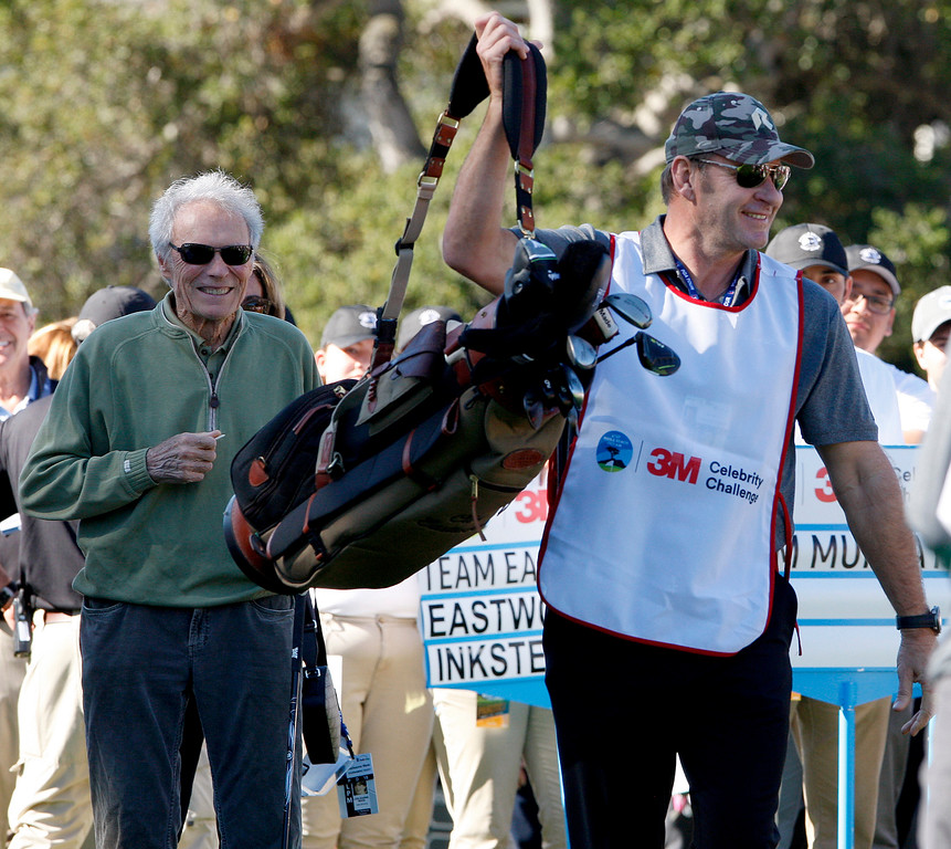 . Clint Eastwood gets former PGA player Nick Faldo to caddy for him during the 3M Celebrity Shoot-Out at the Pebble Beach Golf Links in Pebble Beach on Wednesday, Feb. 7, 2018.   (Vern Fisher - Monterey Herald)