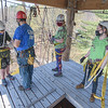 Climbing director Byron Izyk prepares Howard Samples, Maddi Williams, and Emily Prouty for their descent down the rapelling tower.