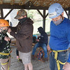 Ben Samples gets equipped for the rapelling tower by dad Walter and climbing staff member Phil Brodeur.