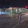 A construction worker guides one of the two spans into position.