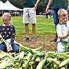 Ripping away at corn during the corn husking contest is L-R, Elsa Swanson 10 of Westford and Malcolm Flaks 7 of Billerica. SUN/ David H. Brow