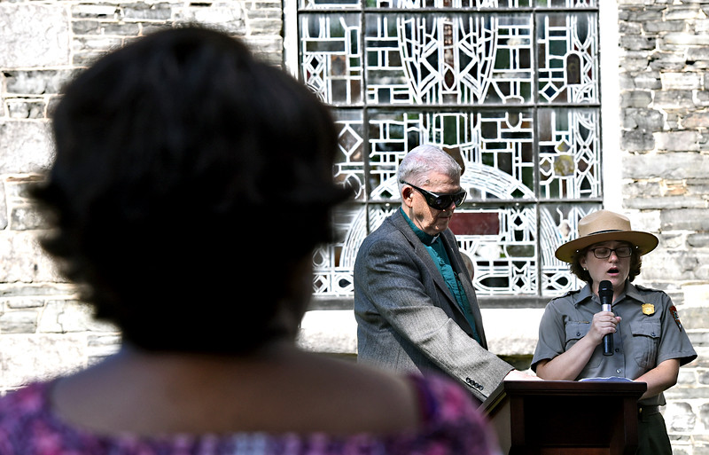 NPS Park Ranger Allison Horrocks speaking at the Commemoration of the 400th year Anniversary of the first enslaved Africans to land in North America, with her is Reverend Richard Lewis in front of St Anne's Church. SUN/ David H. Brow