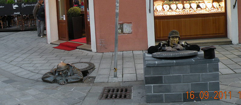 """Cumil (The Watcher) - although this bronze statue does not personify any of the famous people of the rich Bratislava history, it is definitely the most popular piece of art in the city. Where else in the world could you possibly find a man inconspicuously peeping from a street manhole? We were lucky enough to also catch a """"human statue"""" in close proximity. Can you tell who the real """"Cumil"""" is?"""