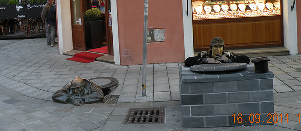 "Cumil (The Watcher) - although this bronze statue does not personify any of the famous people of the rich Bratislava history, it is definitely the most popular piece of art in the city. Where else in the world could you possibly find a man inconspicuously peeping from a street manhole? We were lucky enough to also catch a ""human statue"" in close proximity. Can you tell who the real ""Cumil"" is?"