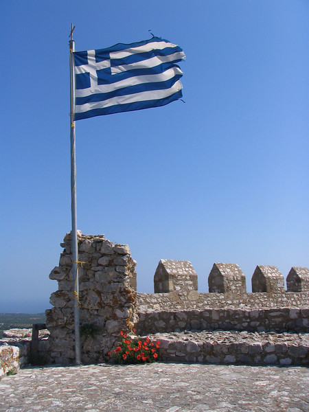 A flag flying proud a top Chlemoutsi Castle, Greece along our ride nearing the end of the trip. It is exposed to the weather and fresh air just as us cyclists!