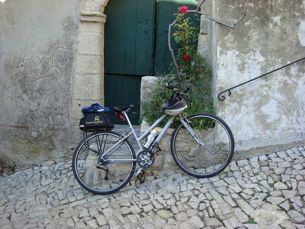 This was my bike (complete with ExperiencePlus bag, my ever-present blue rain jacket and my helmet) --- it looked so pretty with the cobbled streets and the old door and rose arbor behind it.