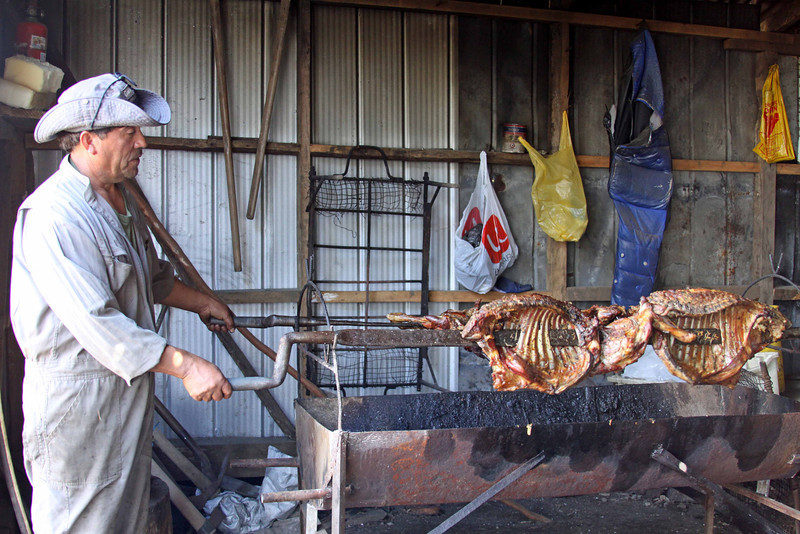 """Cooking lamb at Palqui."" Location is at Palqui on the Island of Quinchao (near Chiloe Island, Chile). We had started the day cycling on Chiloe Island, then took a short ferry to Quinchao Island and took a side road down to the beach where we had a wonderful home cooked meal (featuring this lamb cooked over the coals). The immersion in local culture is a major attraction of bicycle touring, and this experience proved the point (not to mention providing fuel for the climb back to the main road)."