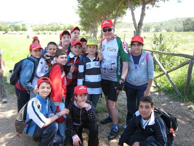 "Hat exchange: I have exchanged my ExperiencePlus bike cap for a red school cap with a boy who was with his classmates on an outing to Etruscan ruins, during May, 2009.  ExperiencePlus's tradition of exchanging caps with locals is a means to meet the ""locals"" when cycling. This exchange was on my tour, Cycling the Coast of Tuscany."