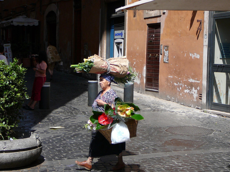 Going to Market.   I went to see the Pantheon in Rome and as I stood outside admiring it's beauty I turned and saw this lady taking her flowers to a small market on a nearby side street.
