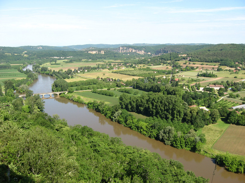 Domme, France A steep climb rewards us with a great view of the Dordogne River Valley from the town of Domme.  Below lies the river, vivid green farmlands and the bridge which will lead us on.  Ahead are enchanting castles and chateaus awaiting our arrival!