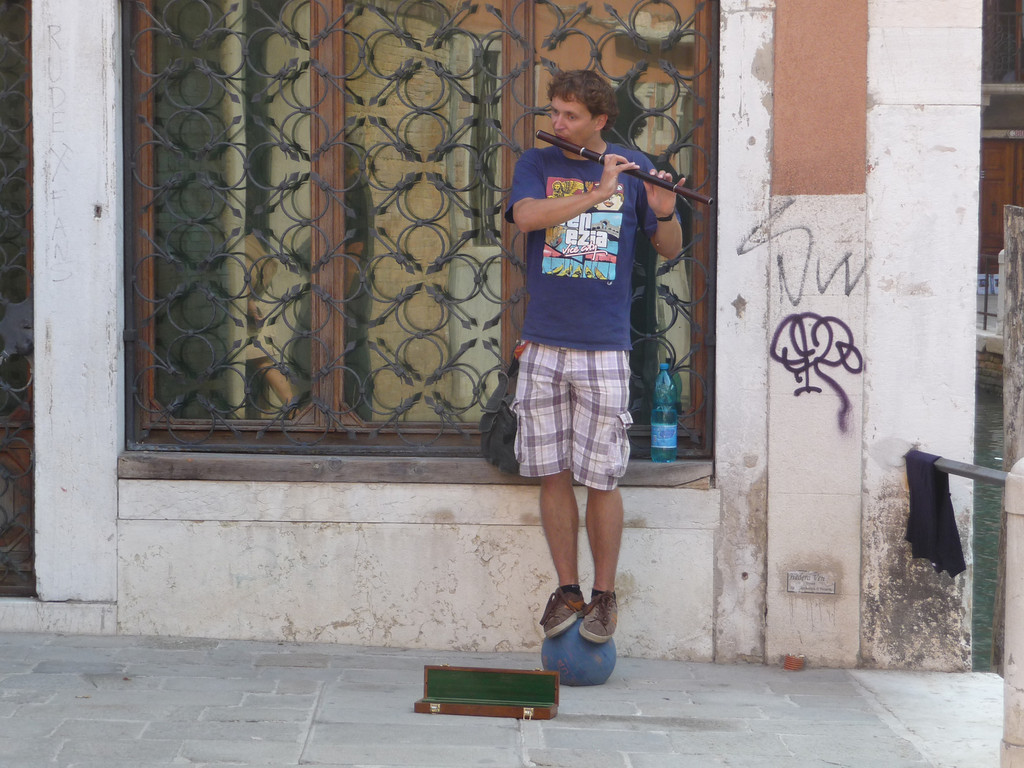 Here is a street performer balancing on a ball, in Venice.