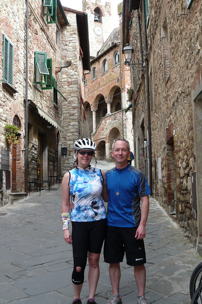 """I like this photo since it shows the great old buildings of Suvereto and is one of the few photos of the two of us during the trip. Plus, for me, seeing us in our bike gear reminds me of how biking to and through these places somehow helps you feel """"more there"""", helps you to experience it more thoroughly."""