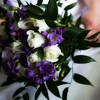 A gorgeous purple and cream colored bouquet of flowers being held in lap by bride.