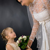 Bride wearing romantic white wedding dress with veil, giving bouquet of flowers to little bridesmaid, smiling.