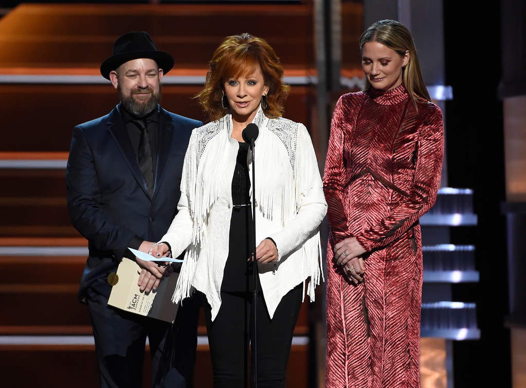 ". Reba McEntire, center, accepts the award for album of the year for ""From A Room: Volume 1\"" on behalf of Chris Stapleton at the 53rd annual Academy of Country Music Awards at the MGM Grand Garden Arena on Sunday, April 15, 2018, in Las Vegas. Looking on are presenters Kristian Bush, left, and Jennifer Nettles, right, of Sugarland. (Photo by Chris Pizzello/Invision/AP)"