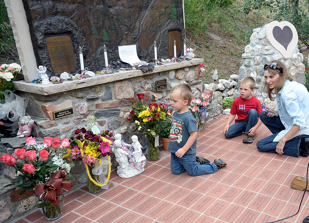 . Linda Marriner, right, shows her gandsons, Colby Marriner, 3, left, and Kaden Marriner, 5, the Big Thompson Flood Memorial Monday, July 31, 2017, before the 41st Big Thompson Flood Memorial ceremony in Drake west of Loveland. Marriner\'s father, Doc Ealy Lee, perished in the flood of 1976.   (Photo by Jenny Sparks/Loveland Reporter-Herald)