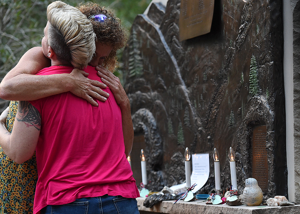 . Tina Anderson, right, hugs Meredith Graham after the two lit candles Monday, July 31, 2017, in memory of the five 1976 flood victims who were never found during the 41st Big Thompson Fllod Memorial ceremony in Drake west of Loveland.   (Photo by Jenny Sparks/Loveland Reporter-Herald)