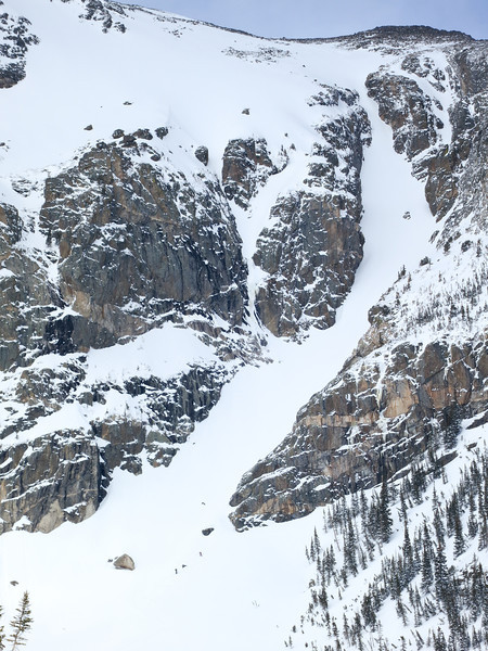 A pair of skiers getting ready to climb the couloir.