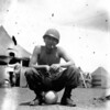 Title: Pau hana time.  Gus Ohashi drinking from cup sitting near tent<br /> <br /> Date:  1945.05.xx to 1945.07.xx<br /> <br /> Location: Ghedi Airfield, Italy<br /> <br /> Notes from Yasunori: Relaxing after another days work.<br /> <br /> Photo courtesy of Yasunori Deguchi. Copyright retained by the Estate of Yasunori Deguchi.
