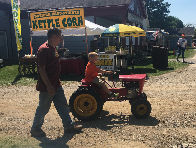 A young tractor enthusiast rides around his mower during the 47th annual Antique Power and Steam Exhibition in Burton, Ohio July 30. (Kailee Leonard/The News-Herald)