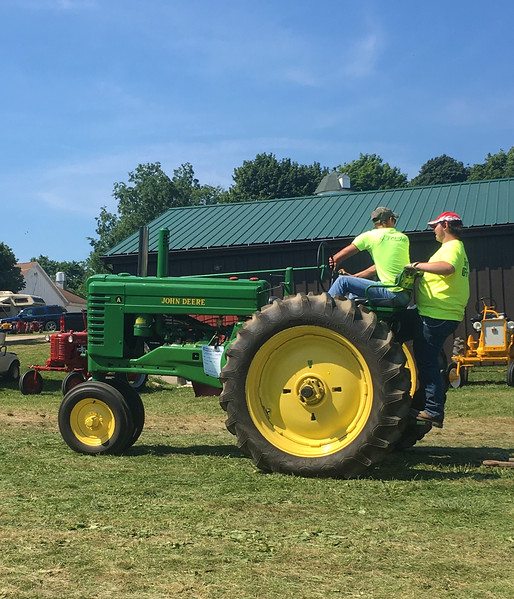 Event staff talk on a John Deere tractor during the 47th annual Antique Power and Steam Exhibition in Burton, Ohio July 30. (Kailee Leonard/The News-Herald)