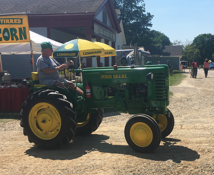 An owner of a John Deere tractor rides around the museum during the 47th annual Antique Power and Steam Exhibition in Burton, Ohio July 30. (Harley Marsh/The News-Herald)