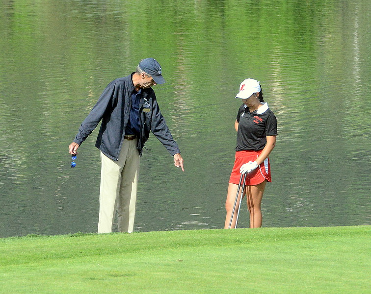 Natalee Hall of Loveland gets a ruling from an official during  the second round of the 4A state girls golf tournament at Country Club of  Colorado in Colorado Springs. (Mike Brohard/Loveland Reporter-Herald)
