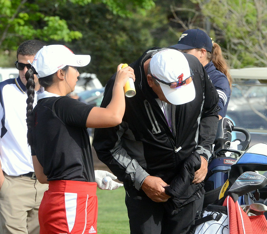 Loveland's Natalee Hall applies sunscreen to coach Bill Stephens prior to the start of Tuesday's second round of the 4A state girls golf tournament at Country Club of  Colorado in Colorado Springs. (Mike Brohard/Loveland Reporter-Herald)