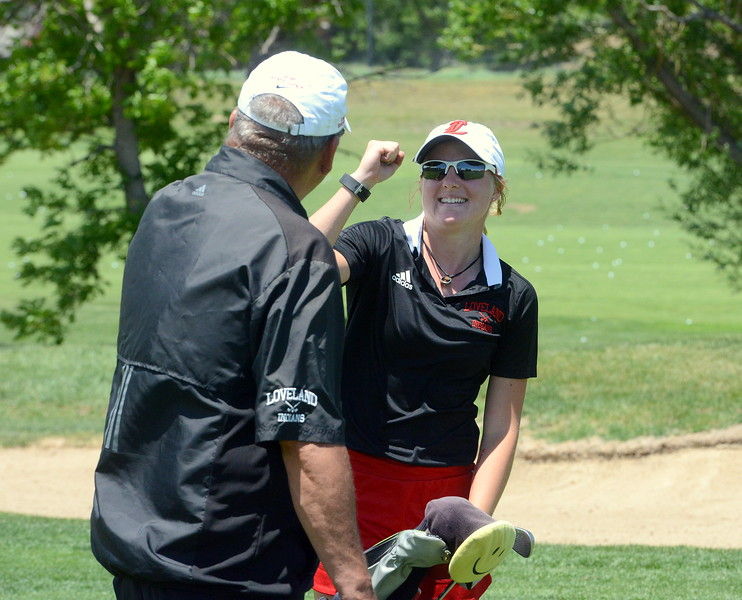 Loveland's Lauren Lehigh gets a fist-bump from coach Bill Stephens after hitting the green from the fairway during Tuesday's second round of the 4A state girls golf tournament at Country Club of  Colorado in Colorado Springs. (Mike Brohard/Loveland Reporter-Herald)