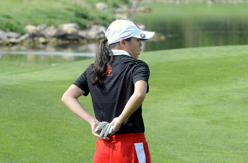 Loveland's Casey Bradley tucks away her golf glove as she gets set to putt on No. 10 during  the second round of the 4A state girls golf tournament at Country Club of  Colorado in Colorado Springs. (Mike Brohard/Loveland Reporter-Herald)