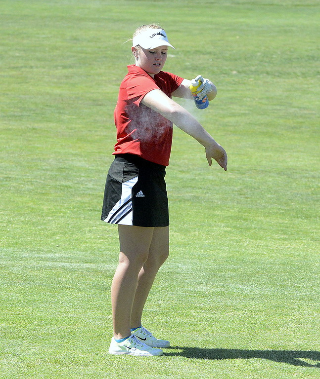 . Loveland\'s Aili Bundy takes a break to apply sunscreen during Friday\'s 4A Region 4 tournament. The senior won the individual title with a 2-over 74 at Murphy Creek Golf Course in Aurora.