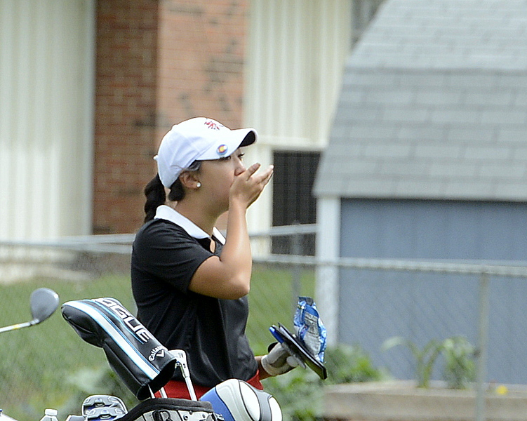 Loveland's Natalee Hall eats a snack during the 4A Region 4 golf tournament Monday at Highland Hills Golf Course in Greeley. (Mike Brohard/Loveland Reporter-Herald)