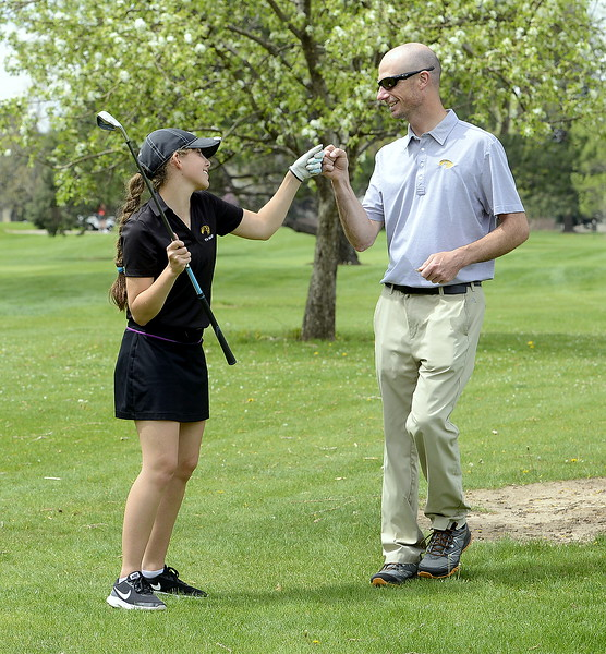 Ryanna Burton of Thompson Valley gets knuckles from coach Derek Shagin after successfully punching out of trouble onto the fairway during the 4A Region 4 golf tournament Monday at Highland Hills Golf Course in Greeley. (Mike Brohard/Loveland Reporter-Herald)