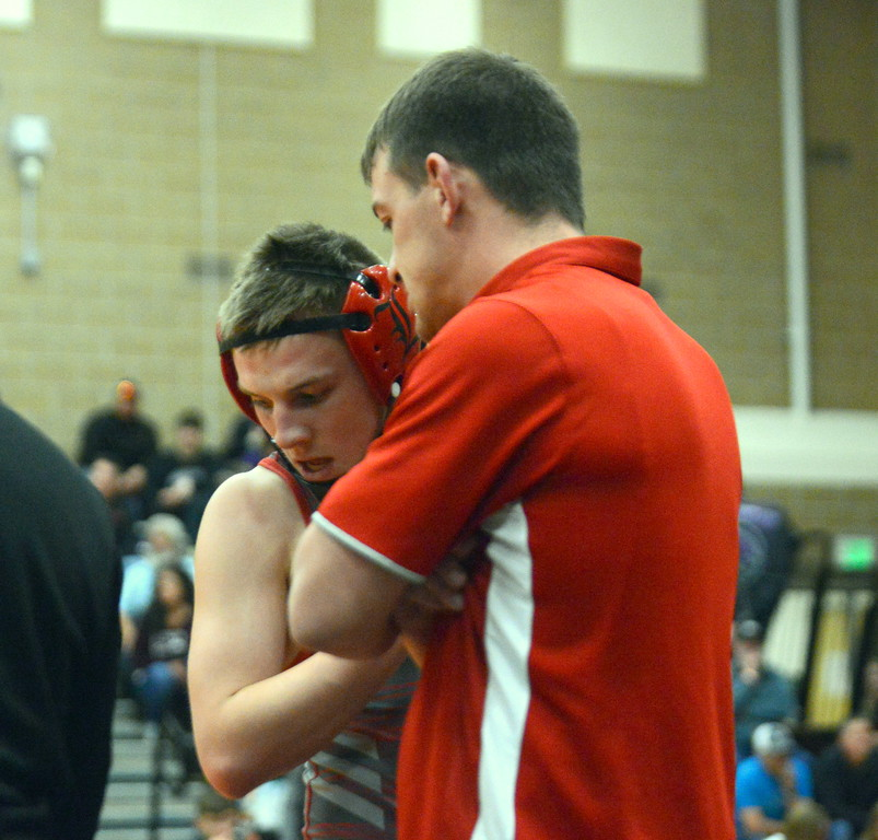 . Loveland coach Troy Lussenhop talks to 126-pounder Isaac Vigil during his loss to Juan Garcia of Roosevelt in the championship match at Saturday\'s 4A Region 4 wrestling tournament at Mead. (Mike Brohard/Loveland Reporter-Herald)