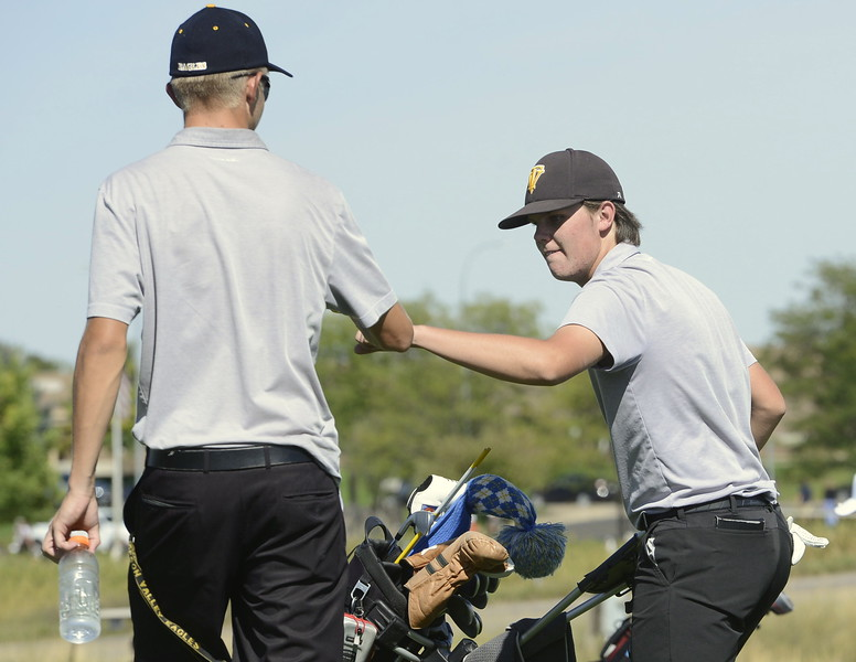 Thompson Valley's Chase Corlett, right, gives a fist bump to teammate Darren Edwards on the 18th hole during the Region 3 tournament at Boomerang Golf Course in Greeley on Tuesday.