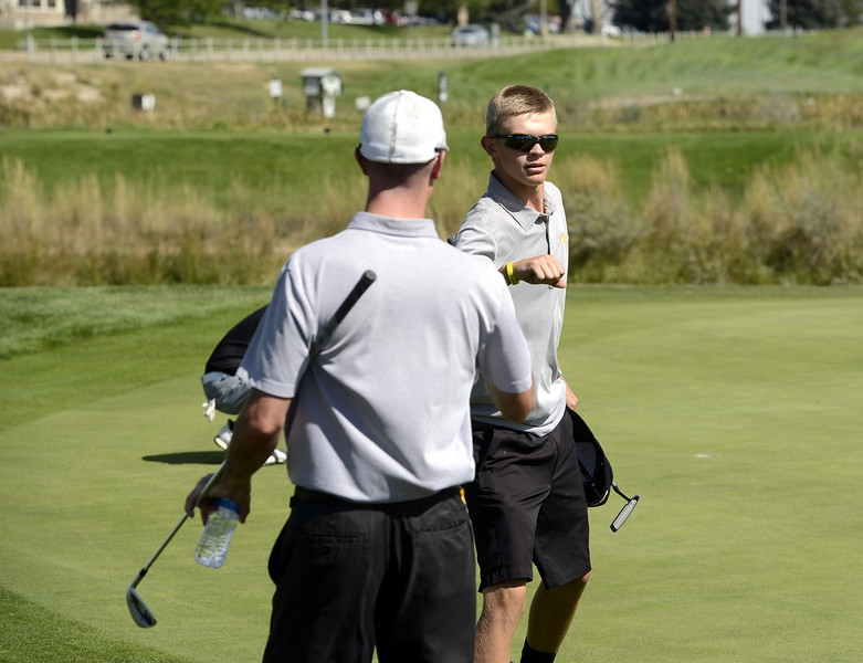 Thompson Valley's Darren Edwards give his coach, Derek Shagin, a fist bump during the Region 3 tournament at Boomerang Golf Course in Greeley on Tuesday.