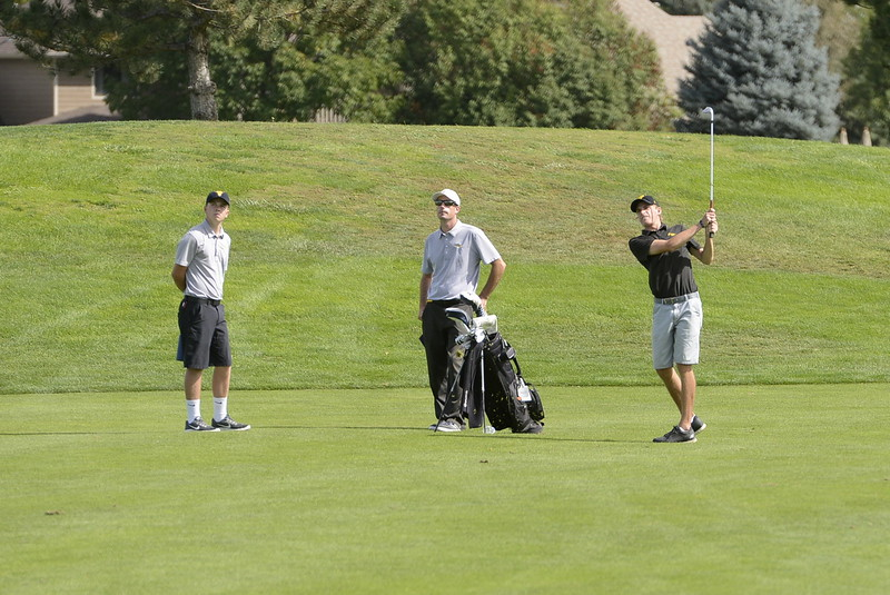 Thompson Valley's Nate Dwyer, right, along with his coach Derek Shagin, middle and teammate, , watch his approach shot on the eighth hole during the 4A Region 3 tournament on Tuesday at Boomerang Golf Course in Greeley.