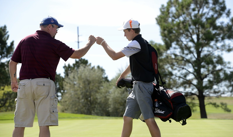 Berthoud coach Mike Burkett, left, gives Cameron Poll a fist bump during the Region 3 tournament at Boomerang Golf Course in Greeley on Tuesday.