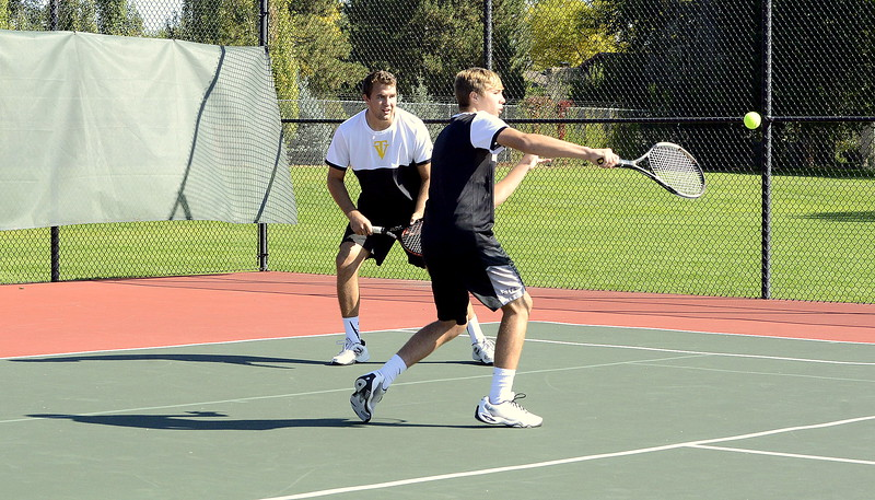 Jared Kasprzak watches from the background as his brother Brody returns a shot during Friday's regional final at No. 2 doubles in Greeley. The Thompson Valley pairing beat Dawson 6-4, 6-4.