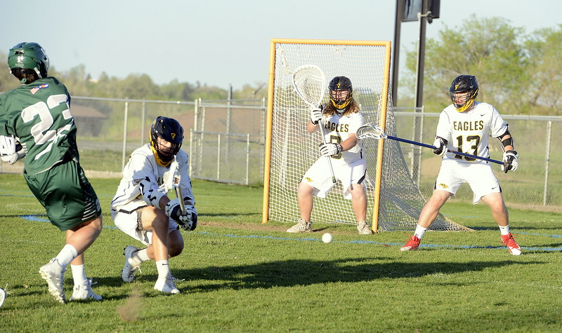 Thompson Valley's Evan Vaughn disrupts the shot of Summit's Matt Duxbury as teammates Corbin Shilling (0) and Travis Bretches look on Tuesday's 4A boys lacrosse state playoff game at Patterson Stadium. (Mike Brohard/Loveland Reporter-Herald)