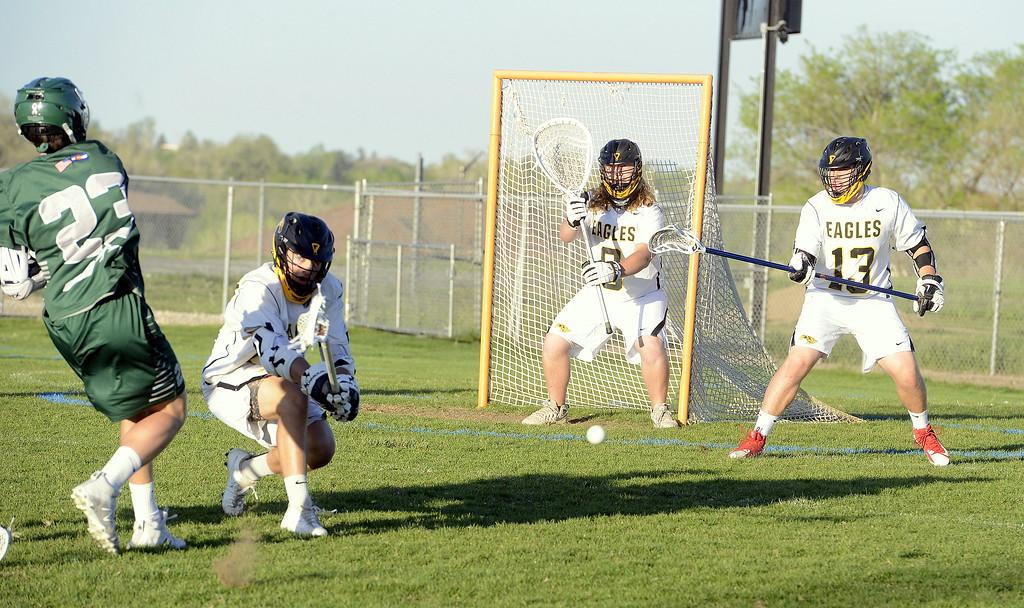 . Thompson Valley\'s Evan Vaughn disrupts the shot of Summit\'s Matt Duxbury as teammates Corbin Shilling (0) and Travis Bretches look on Tuesday\'s 4A boys lacrosse state playoff game at Patterson Stadium. (Mike Brohard/Loveland Reporter-Herald)