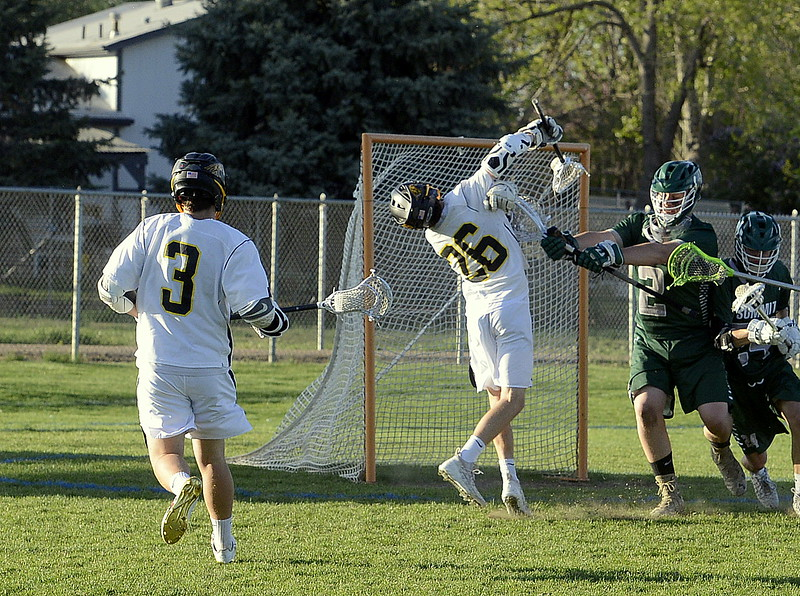Thompson Valley's Greg Bilek gets a faceful of stick for his goal-scoring efforts from Summit goalieSawyer March during Tuesday's 4A boys lacrosse state playoff game at Patterson Stadium. (Mike Brohard/Loveland Reporter-Herald)