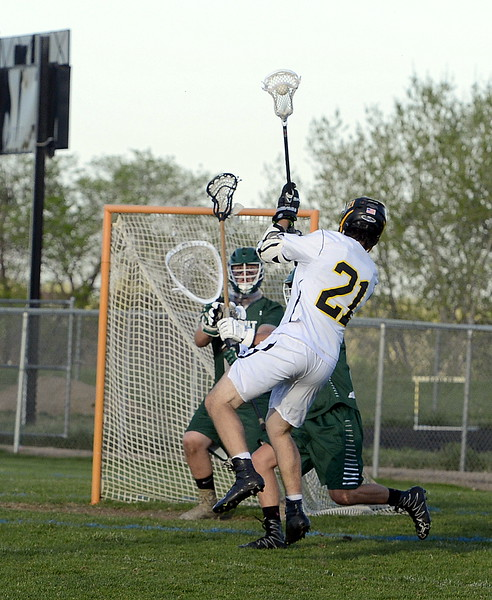 Thompson Valley's Micah Payton goes airborne to get off his shot and score a goal during Tuesday's 4A boys lacrosse state playoff game at Patterson Stadium. (Mike Brohard/Loveland Reporter-Herald)
